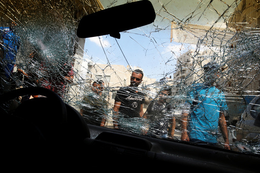 Palestinians surround the car of Palestinian Mustafa Nimer, who Israeli police said attempted to ram policemen and was consequently shot and killed this morning by Israeli security forces, in the refugee camp of Shuafat camp near Jerusalem