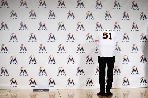 Japan's outfielder Suzuki, wearing his new Marlins hat and jersey, poses for pictures as he is asked to show his number during news conference to announce an agreement on a one-year contract with the Miami Marlins, in Tokyo