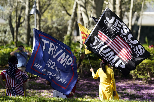 Former President Donald Trump supporters wave flags outside the convention center at the Conservative Political Action Conference (CPAC) Sunday, Feb. 28, 2021, in Orlando, Fla. (AP Photo/John Raoux)