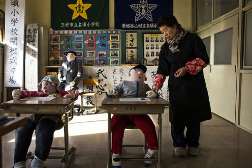 Tsukimi Ayano stands in a classroom with scarecrows at a closed down school in the village of Nagoro