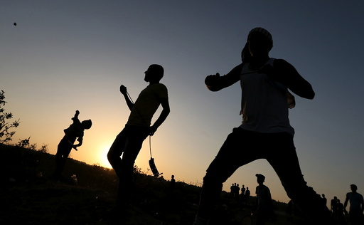 Palestinian protesters hurl stones at Israeli troops during clashes near the border between Israel and Central Gaza Strip
