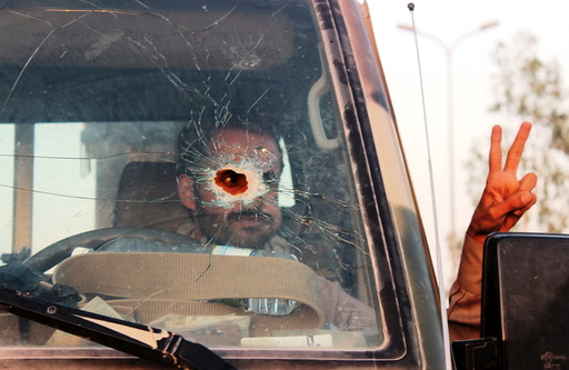 Yemeni soldier, pictured through a vehicle's windscreen, which was damaged by a bullet, gestures out of the window, in Marib, Yemen