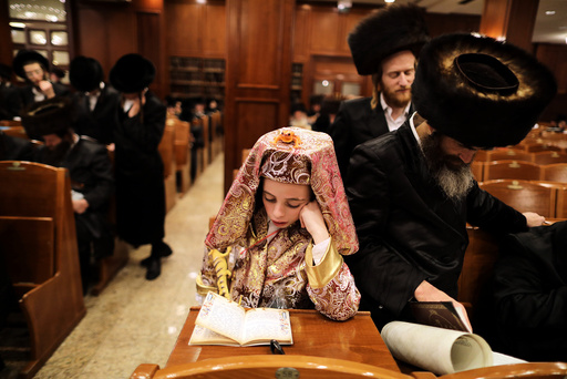 A boy, dressed up in Purim costumes, takes part in the reading from the Book of Esther ceremony performed on the Jewish holiday of Purim, in Jerusalem