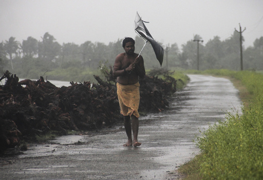 A man struggles with an umbrella in strong winds and rain caused by Cyclone Hudhud in Gopalpur in Ganjam district