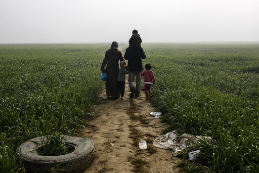 A family walks through a field at a makeshift camp for migrants and refugees at the Greek-Macedonian border near the village of Idomeni