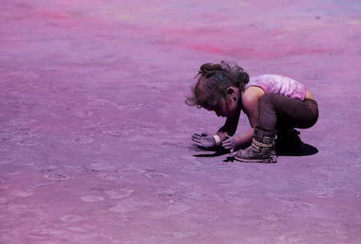 A child scoops up coloured powder from the ground during the Holi Festival of Colours organised by the Maltese-Indian community in Qormi