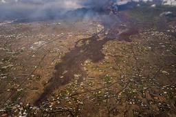 Elver av lava har i flere dager strømmet nedover åssidene og ødelagt hundrevis av hus på den spanske kanariøya La Palma. Fredag ble flytrafikken stanset. Foto: AP / NTB