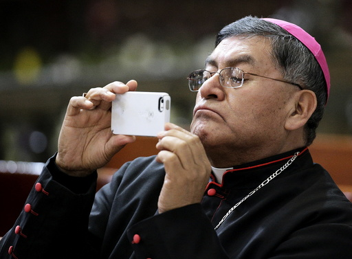 A bishop uses a mobile phone during a meeting with Pope Francis at the Metropolitan Cathedral in Zocalo Square in Mexico City
