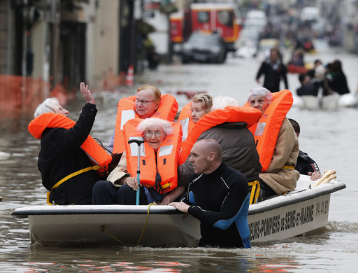 French firefighters on small boats evacuate residents from a flooded area after heavy rainfall in Nemours