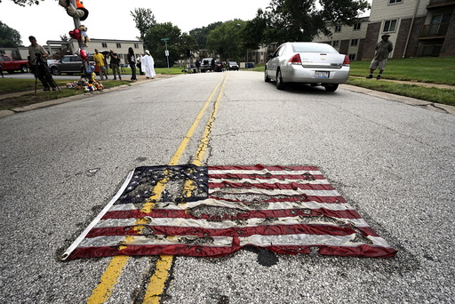 Partially burned American flag lies on the street near the spot where Michael Brown was killed before an event to mark the one-year anniversary of the his death in Ferguson