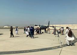 Taliban-medlemmer gikk rundt ute på rullebanen på flyplassen i Kabul tirsdag. Foto: Kathy Gannon / AP / NTB