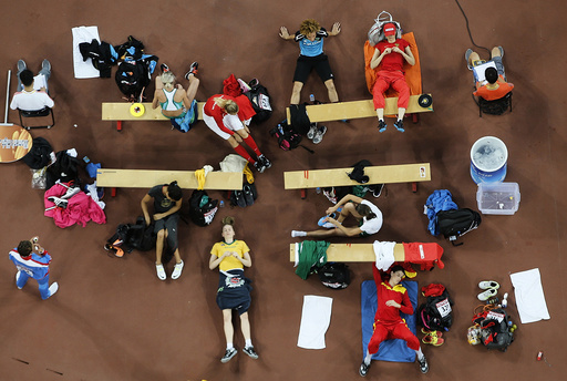 Athletes wait for their turns at the women's high jump final during the 15th IAAF World Championships at the National Stadium in Beijing