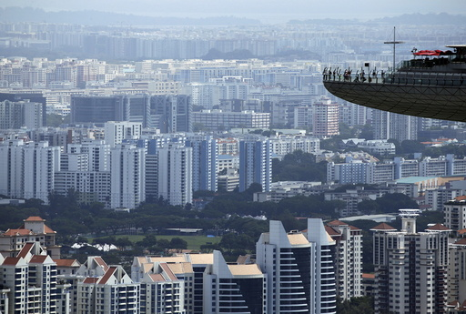 People look out from the observation tower of the Marina Bay Sands amongst public and private residential apartment buildings in Singapore