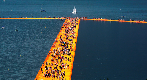 People walk on the installation 'The Floating Piers' by Bulgarian-born artist Christo Vladimirov Yavachev, known as Christo, on the Lake Iseo