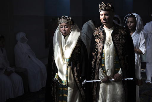 A bride and groom wearing traditional Eritrean dress arrive for their wedding at a Christian Orthodox church in Jerusalem