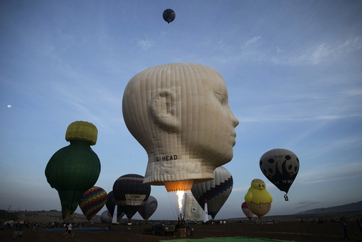 Hot air balloons are prepared for a flight as others take off during an international hot air balloon festival at Maayan Harod National park in northern Israel