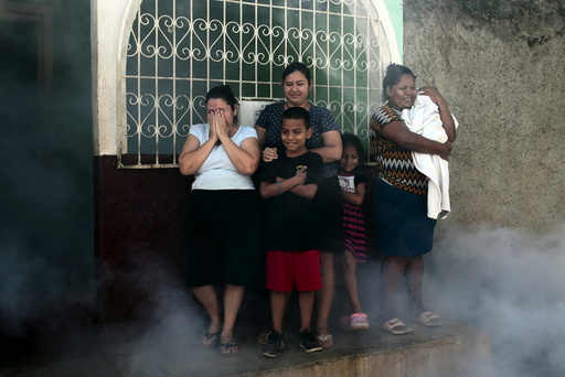 People stand outside their house while a health ministry worker fumigates to kill mosquitoes during a campaign against dengue and chikungunya in Managua