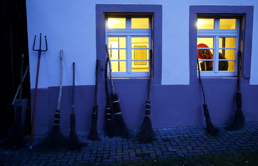 A carnival reveller dressed as a witch (Kandelhexe) looks out of a window as a group of traditional witches meet prior to their traditional witches sabbath performance in the Black Forest village of Waldkirch