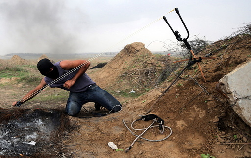 Palestinian protester uses sling shot to hurl stones at Israeli troops during clashes near border between Israel and Central Gaza Strip