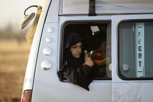 An Iraqi refugee girl that fled violence in Mosul rides a van upon arrival in al-Kherbeh village