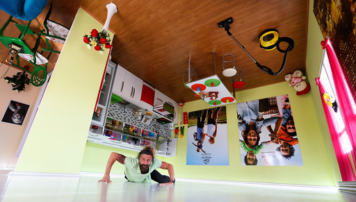An employee poses for visitors inside an upside-down house in the Mediterranean resort city of Antalya