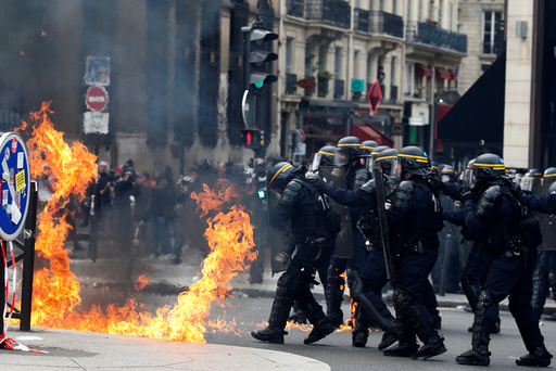 French CRS riot police protect themselves from flames during clashes at the traditional May Day labour union march in Paris