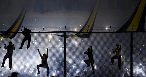 Boca Juniors' fans climb onto the tribune fence as they cheer their team on before their Copa Libertadores soccer match against River Plate in Buenos Aires