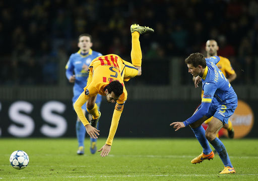 Barcelona's Sergio Busquets falls down onto pitch next to BATE Borisov's Gaiduchik during their Champions League group E soccer match at Borisov Arena stadium outside Minsk