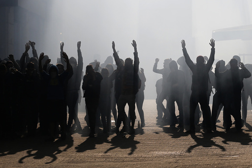 Tear gas fills the air as masked and hooded demonstrators put their hands in the air as they are surrounded by French police and gendarmes at the end of a demonstration against the French labour law proposal in Nantes