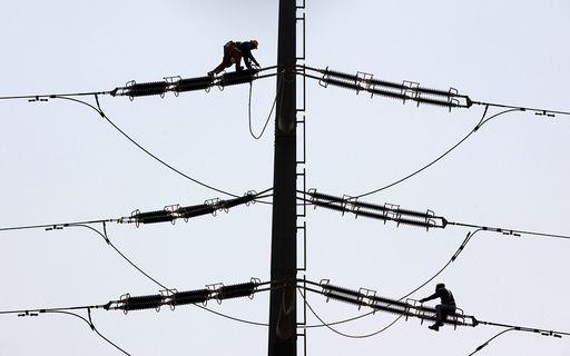 Employees of K-Electric fix cables on a power transmission tower in Karachi,