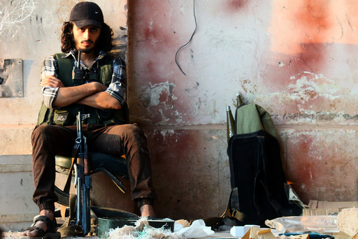 A rebel fighter sits with his weapon in the artillery academy of Aleppo