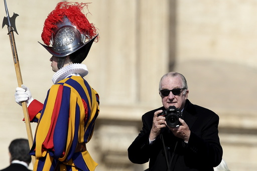 Belgium's King Albert II holds a camera in St. Peter's square before Pope Francis leads the Easter mass at the Vatican