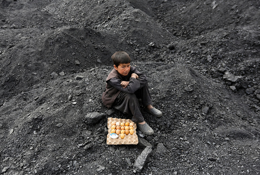 An Afghan boy selling boiled eggs waits for customers at a coal dump site on the outskirts of Kabul