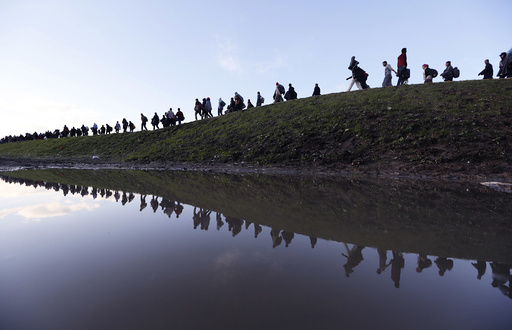 Migrants make their way on foot on the outskirts of Brezice