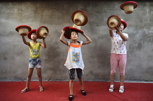 Students toss hats as they practice at an acrobatic school in Sanwang village