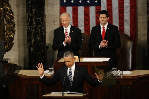 U.S. President Barack Obama reacts to cheers as he arrives at the podium to deliver his State of the Union address to a joint session of Congress in Washington