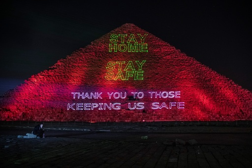 A journalist looks at his mobile phone as the Ministry of Antiquities lights up the pyramids in an expression of support for health workers battling the coronavirus outbreak, Monday, March 30, 2020, in Giza, Egypt. (AP Photo/Nariman El-Mofty)