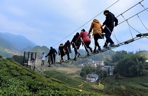 Tourists walk above a tea plantation in Enshi