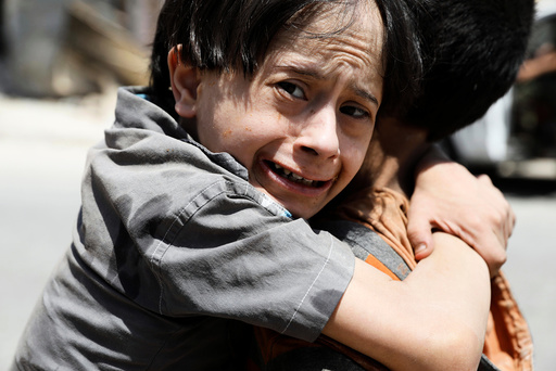 Displaced Iraqi boy carries his brother to a field hospital after they were rescued by Iraqi forces from battle at the the Old City in Mosul