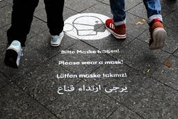 Tyske fotgjengere får en vennlig påminnelse om å bruke munnbind på fortauet i Karl-Marx-Strasse i Berlin. Foto: Markus Schreiber/AP/NTB