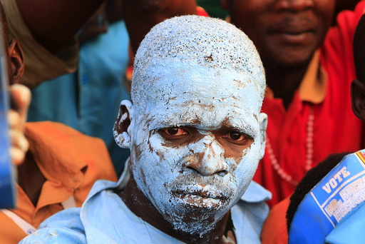 A supporter of Uganda's main opposition presidential candidate Besigye of the FDC coloured himself blue in the FDC's party colour during a campaign rally in Lira town