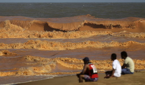 Men look on from the banks of Rio Doce (Doce River), which was flooded with mud after a dam owned by Vale SA and BHP Billiton Ltd burst, as the river joins the sea on the coast of Espirito Santo in Regencia Village, Brazil