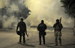 Politibetjenter står oppstilt mot demonstranter, mens tåregassen ligger tett over Ettadhamen like ved Tunis tirsdag. Demonstrasjonene foregår daglig. Foto: Hassene Dridi / AP / NTB