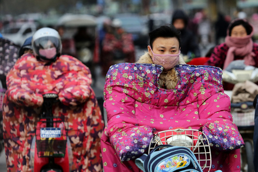 People wear special jackets made for riders to keep out the wind during a cold day in Lianyungang