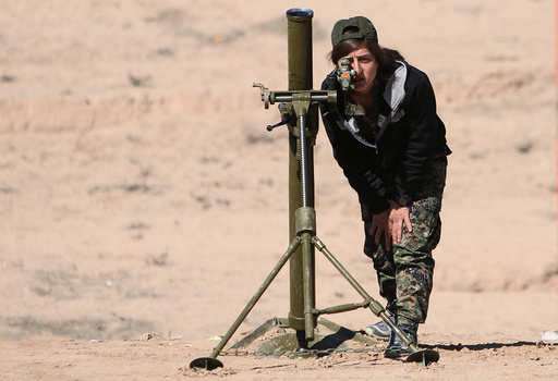 A Syrian Democratic Forces (SDF) female fighter adjusts a mortar in northern Deir al-Zor province ahead of an offensive against Islamic State militants