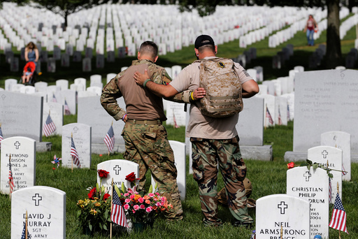 U.S. Army soldiers Rick Kolberg and Jesus Gallegos embrace as they visit the graves of Raymond Jones and Peter Enos on Memorial Day at Arlington National Cemetery in Washington