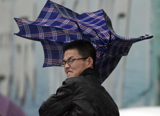 A man's umbrella is blown by wind during a heavy rain in Yantai