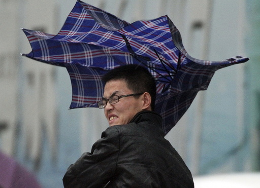 A man's umbrella is blown by wind during a heavy rain in Yantai