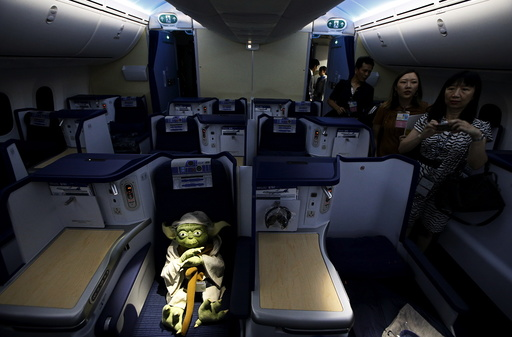 Visitors look at a Yoda plush toy sitting in the business class section during a tour of the