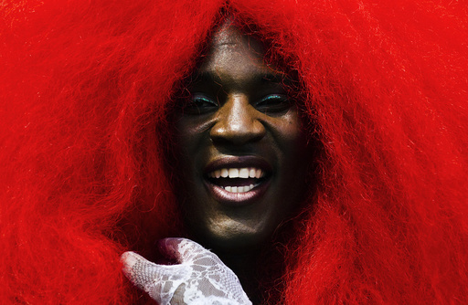 A person wears a giant red wig as the take part in the Gay Pride Parade in Toronto